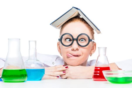 a chemist in funny glasses shows his tongue, on a table a flask with colored substances