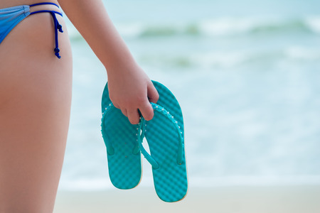 flip flops in the hand of a girl on the beach closeup