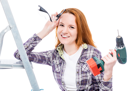 decorating: Happy housewife with tools wearing a plaid shirt, a portrait on a white background
