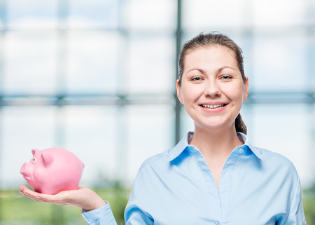 horizontal portrait of a successful woman with a pink piggy bank and space for writing in office