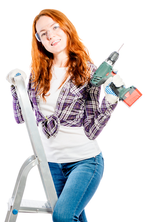 beautiful girl with red hair on a stepladder with a drill pose Foto de archivo