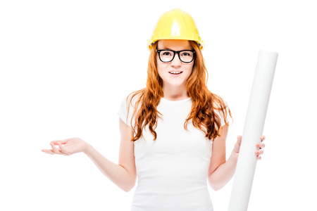 young beautiful red-haired woman with blueprints in a yellow hard hat against a white background