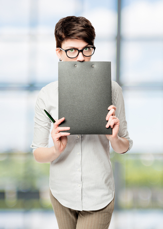 Business woman hiding behind a black folder in the office