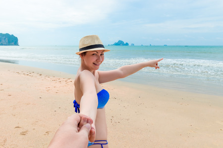 girl in bikini and hat shows off somewhere in the sea