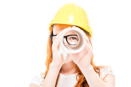 Portrait of a woman builder who looks through blueprints as in a telescope on a white background