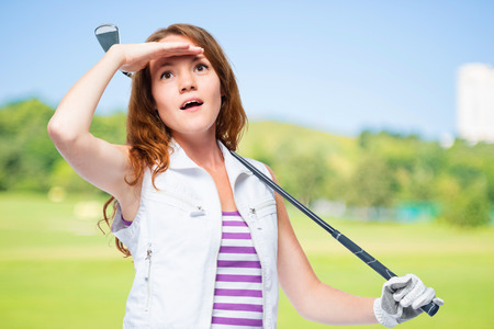 Watching the flight of a golf ball on a background of golf courses