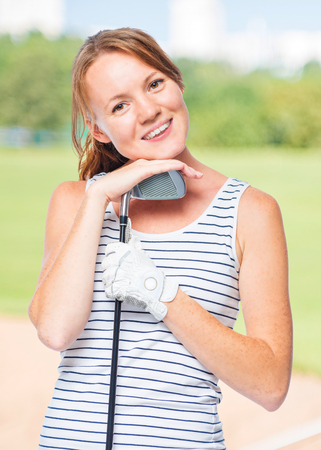 Cute girl with a golf club on a background of golf courses in a striped T-shirt Stock Photo