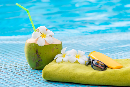 edge: green towel and beach accessories near to a juicy coconut decorated with flowers on the edge of the pool