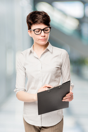 professional accountant with folder reads a document in the office Stock Photo