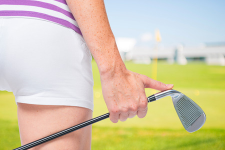 A golf club in the hands of a young female athlete close-up on a background of golf courses