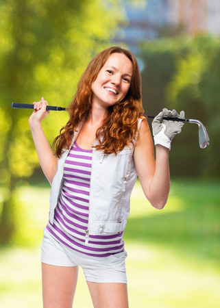 Happy young athlete with a golf club posing on a background of golf courses Stock Photo