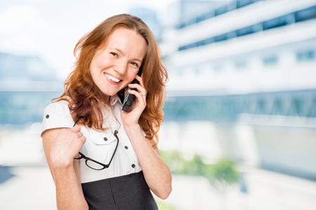 Happy businesswoman talking to the phone in the office Stock Photo