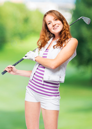Smiling sportswoman with golf club on a background of golf courses Stock Photo