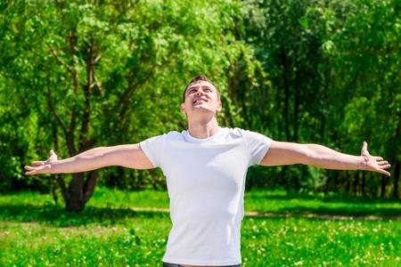 Homem feliz, de braços abertos em um parque ensolarado de verão Foto de archivo - 90168022