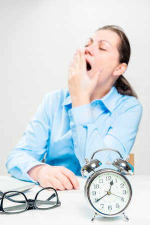 Tired yawning woman in an office out of focus and an alarm clock closeup Stock Photo