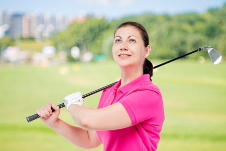 Horizontal portrait of a successful golfer with equipment for playing golf on a background of golf courses