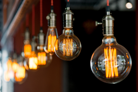 light bulb hanging from the ceiling in a retro style closeup in darkness