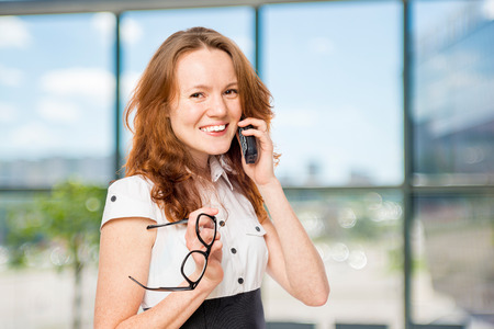 Horizontal portrait of an office worker with a phone consultant