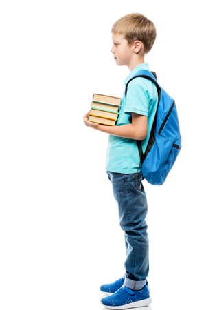 schoolboy with a bunch of books and a backpack on a white background in full length side view