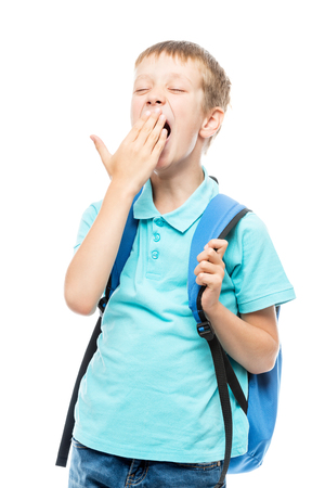 yawning schoolboy covers his mouth with his hand on a white background portrait isolated