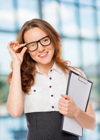 successful woman corrects glasses in the office Stock Photo