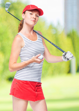 Slender sportswoman golfer with stick and ball on a background of golf courses Stock Photo