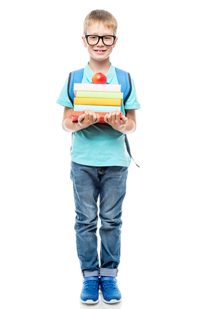 smart schoolchild with glasses with a pile of books and an apple on a white background isolated