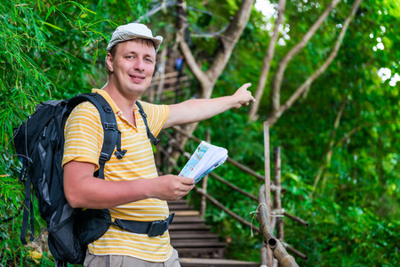 tourist with a backpack in the Asian jungle in the hike shows the direction of the route Фото со стока