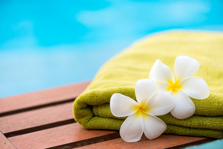 green terry towel on a chaise longue close up and two flowers frangipani