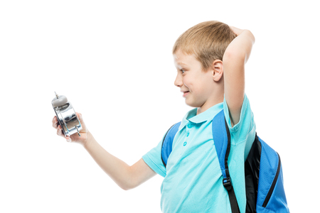 surprised schoolboy looking at alarm clock on white background