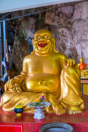 golden sculpture of a fat deity in the temple of Thailand