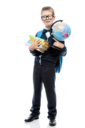 8-year-old schoolboy with a globe and books on a white background in full length Stock Photo