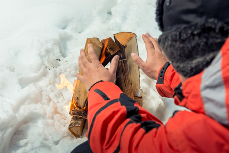 close-up photo - tourist warms his hands near the fire in the winter forest Stock Photo