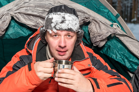 portrait of a frozen man with snow on a hat with hot tea in a camping Stock Photo