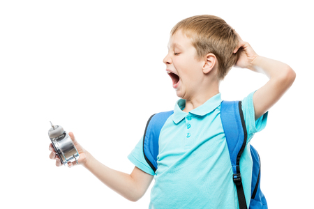 tired yawning schoolboy with an alarm clock on white background Stock Photo