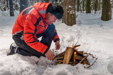 a lost frozen tourist tries to build a fire in a winter cold forest Stock Photo