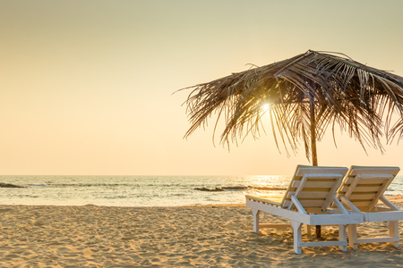 empty chairs under thatched umbrellas on a sandy beach. Tinted.