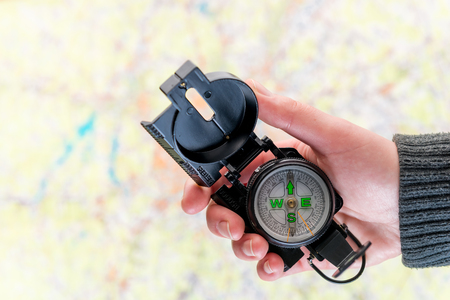 compass in a female hand to search for missing people on a background map - concept of a volunteer