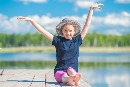 girl in a hat sits on a wooden pier near a lake and poses
