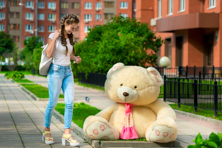 happy girl and a huge teddy bear outdoors in the city
