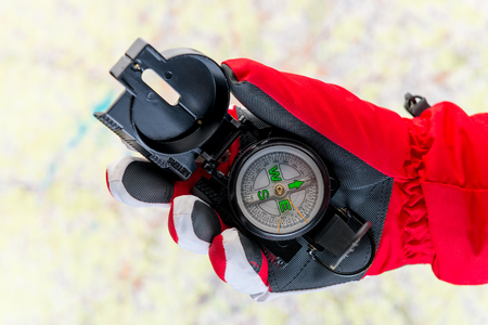conceptual photo - search for missing tourists in the mountains in winter - a hand in the glove holds a compass on the background of the map Stock Photo