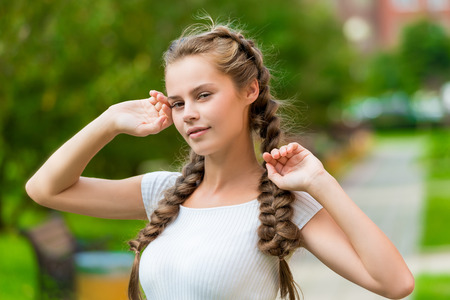 charming girl with two braids close-up portrait in the park