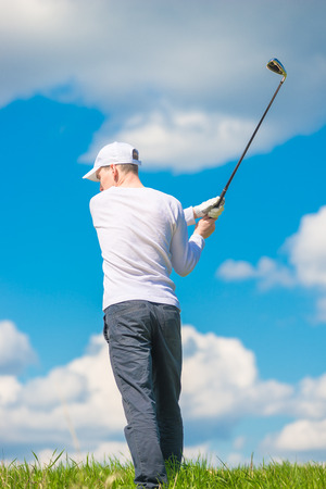 man swinging his club before hitting the ball against the blue sky Stock Photo
