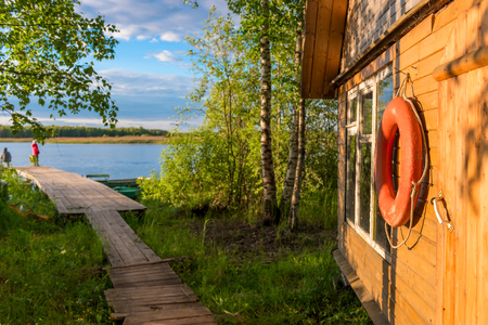 close-up of an old lifebuoy on a wooden wall of a rural house near a lake