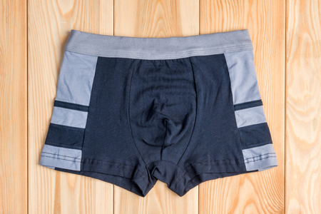 quality cotton panties for boy clothes on wooden boards top view