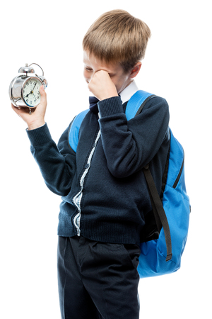 crying little boy in school uniform with an alarm clock on white background Stock Photo