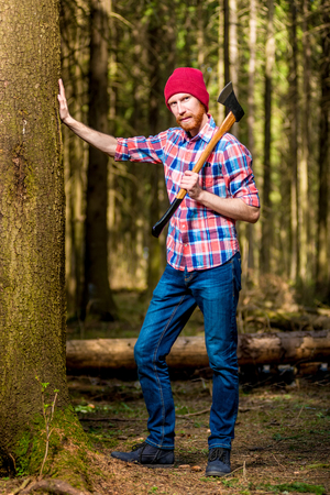 vertical portrait of a full-length bearded lumberjack with an ax near a tree in the woods Stock Photo