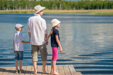 Dad with his son and daughter admiring the beautiful scenic lake, the view from the back