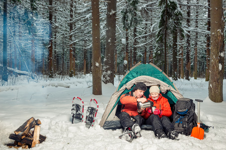 desperate tourists with tea at halt in the winter cold forest Stockfoto