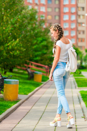 stylish young girl is walking around the city with a backpack, rear view Stock fotó